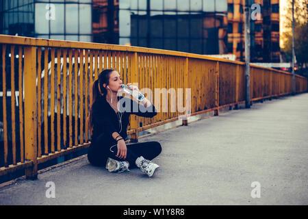 Corredoras sentado en el puente y beber agua de una botella. Fitness mujer tomando un descanso después de ejecutar el entrenamiento.