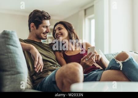 Tierna pareja sentada en un sofá en casa. El hombre y la mujer en el sillón relax con el smartphone en la sala de estar. Foto de stock