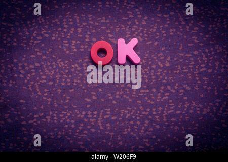 La palabra OK con coloridos bloques de letras sobre tela