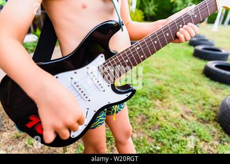 Detalle de una guitarra eléctrica, celebrado por un niño en el patio de su casa en sus vacaciones de verano.