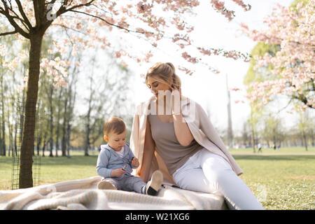 SAKURA Cherry Blossom - joven mamá madre sentada con su pequeño muchacho hijo en un parque en Riga, Letonia Europa