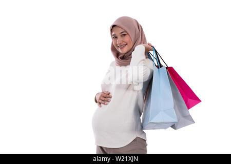 Mujer embarazada muestran un montón de bolsas de la compra después de comprar en un fondo aislado