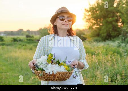 Mujer madura caminando con una canasta y flores en una pradera de verano, hora dorada.