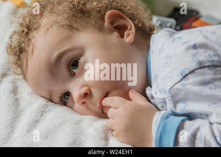 Adorable dos años cabrito en pijama suave con colores azul y cone en la soleada habitación de los niños. El sueño del niño concepto, enfoque suave.
