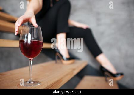 Mujer joven tiene problemas con el alcohol. Cortar la vista de modelo alcanzando mano a cristal con vino tinto. Sentado sobre los pasos solos. Negro elegante traje femenino