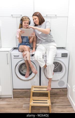 La joven madre y su hija están jugando con la tableta en lavadero sentado en lavadora
