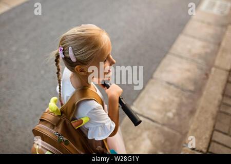 Kid alumna desde detrás caminando de regreso a casa después de la escuela de estudio de aprendizaje solo con mochilas escolares y preescolares, el kindergarten el concepto de educación. Primera