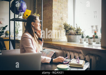 Feliz empresaria habla por teléfono. Mujer en el café, el uso del teléfono móvil, trabajando en el portátil. Señora en la cafetería mediante teléfono y portátil, bebida cup