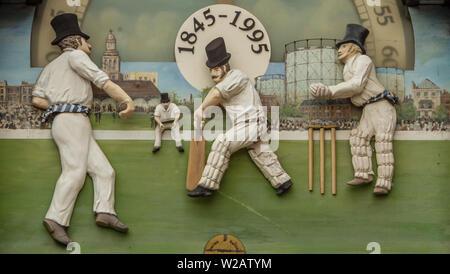 Londres, Reino Unido. El 7 de julio, 2019. Cricket figura detalles sobre el viejo reloj situado a la entrada de miembros antes del primer día del condado de Specsavers juego de campeonato entre Surrey y Kent en el Kia Oval. David Rowe/Alamy Live News