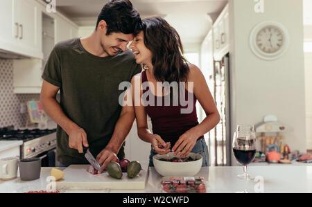 Pareja joven amante cortar verduras juntos en la cocina. Joven Hombre y mujer enamorada cocinar comida juntos en casa. Foto de stock