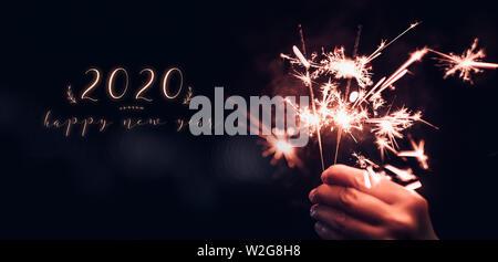 Feliz año nuevo 2020 texto con mano sujetando la quema de fuegos artificiales en Bengala blast con un bokeh de fondo negro en la noche,la celebración parte de eventos,d