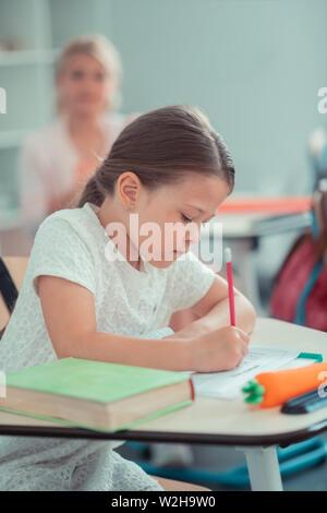 Colegiala trabajando duro en su prueba de matemáticas.