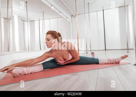 Mujer concentrada haciendo pierna-split en el gimnasio.