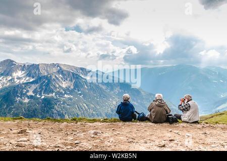 Tatras polaco, Polonia el 3 de junio de 2019: tres ancianos con mochilas están sentados en las montañas. El viejo mira a través de binoculares. La pareja e