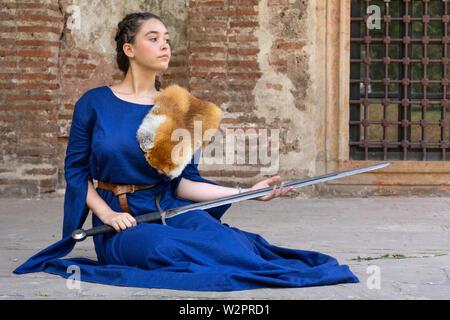 Nis, Serbia, el 15 de junio. 2019 dama medieval en un vestido azul con fox fur en hombros sostiene una espada en sus manos y se sienta en el suelo