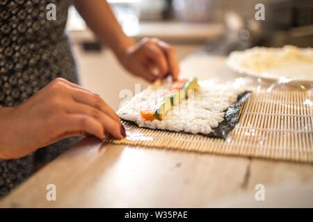 Una mujer preparando y rollos de sushi casero. Formando el sushi. Vista de proceso de preparar sushi de laminación.