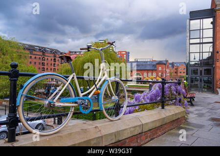 Manchester, Reino Unido - 25 de abril de 2019: Escena atmosférica de una bicicleta estacionada en el sistema de canal Victoriano restaurado en área de Castlefield Manc