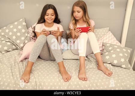 Smartphone para entretenimiento. Kids Play móvil smartphone aplicación de juego. Concepto de aplicación de Smartphone. Ocio Girlish Pajama Party. Las niñas poco smartphone bloggers. Explore la red social.