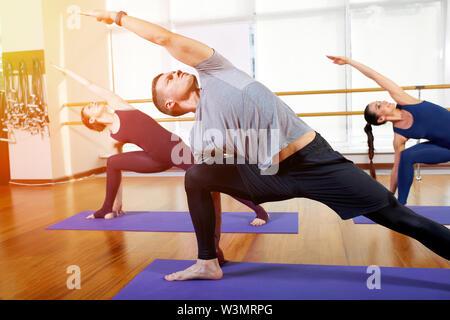 Fitness, yoga y vida saludable el concepto - un grupo de personas que hacen ejercicios de estiramiento y meditación en diferentes posiciones de yoga.