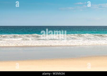 Playa aislada en una isla tropical, con el mar en calma, el cielo azul y el horizonte visible. Destino de ensueño para las vacaciones/vacaciones y pasar el tiempo de ocio. Foto de stock