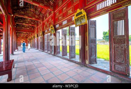 Los turistas visitan a pie a lo largo de pasillos de madera pasillos del Palacio Thai Hoa en la Ciudad Imperial de Hué, Vietnam.