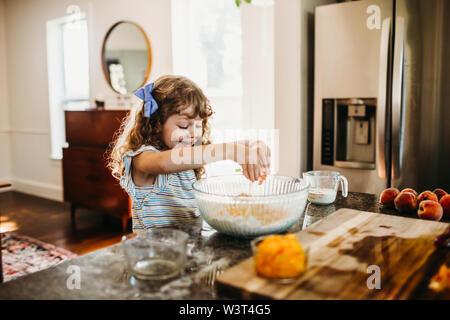 Joven sonriente y agrietamiento en huevo crudo de melocotón fresco muffin bateador Foto de stock