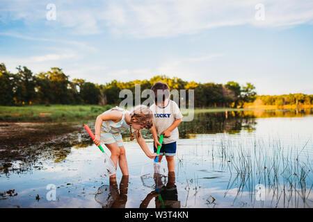 Niña ayudando a boy atrapar un pez en su red en el lago