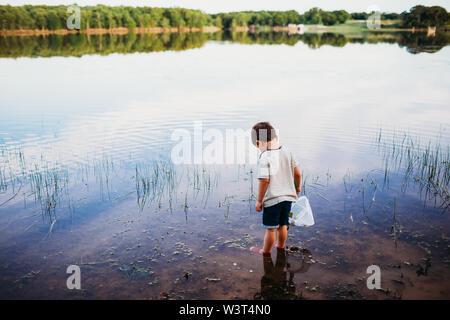 Joven de pie en el lago solo buscando pescado