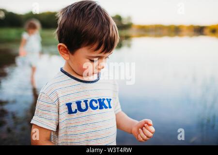 Primer plano de un joven de pie en el agua en el lago en verano