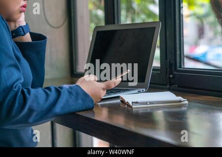 Mujer Asiática sentado delante del portátil y el uso de teléfono móvil