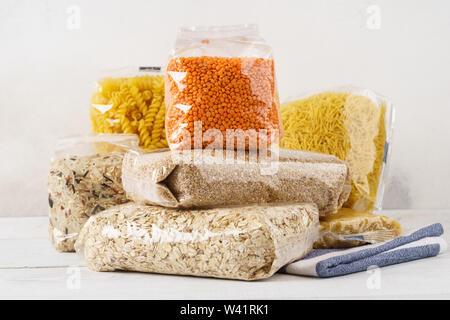 Diversas materias grañones, cereales y pasta en bolsas de plástico transparentes sobre una mesa de cocina. Ingredientes para cocinar.