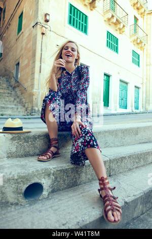 Feliz joven posando en las escaleras en la Valeta, Malta