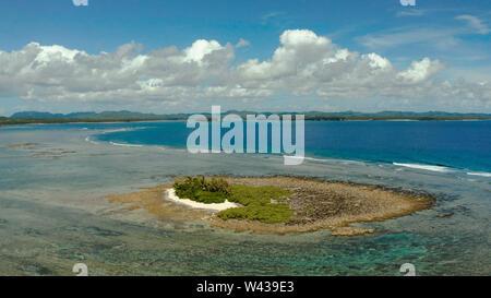 Seascape antena: isla tropical con palmeras y playa en marea baja contra el cielo y las nubes, vista aérea. Filipinas, Siargao. Concepto de vacaciones de verano y viajes