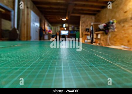 Una visión más cercana sobre la cuadrícula verde superficie de corte en una mesa de dibujo técnico dentro de un atelier. Líneas conducen a un fondo borroso con copia espacio en la parte superior.
