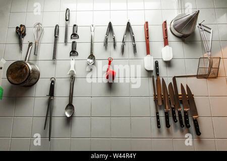 Una visión más cercana de los utensilios de cocina colgados en una pared de mosaico dentro de un restaurante de cocina, herramientas profesionales están perfectamente organizados para fácil acceso