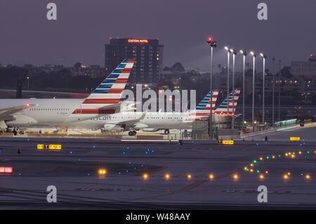 Imagen que muestra varios chorros de American Airlines estacionado en el Aeropuerto Internacional de Los Angeles al atardecer.