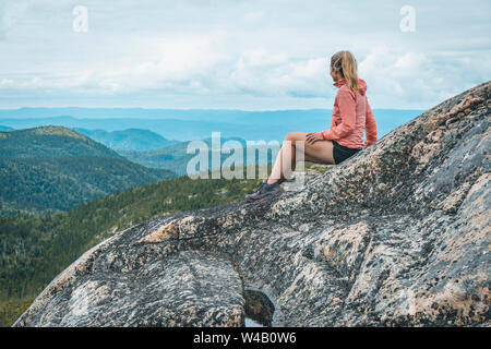 Hembra Trail Runner descansando sobre la cresta de la Montaña en Saguenay
