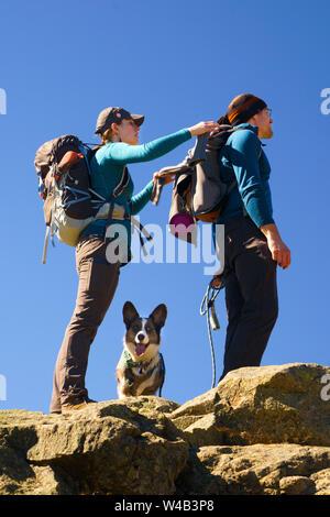 Senderismo par en la cima de una montaña con su Welsh Corgi Cardigan.