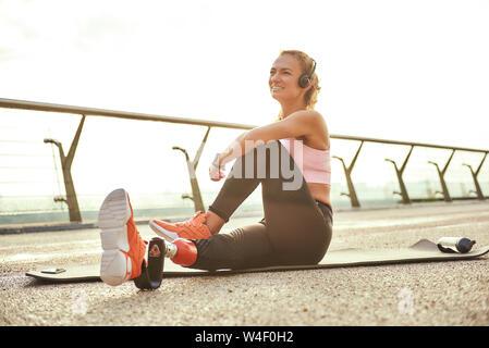Feliz por la mañana. Atletas discapacitados positiva mujer con pierna prostética en auriculares haciendo ejercicios de yoga y sonriendo mientras estaba sentado en el puente. Deshabilitado el deporte concepto. La motivación. Estilo de vida saludable
