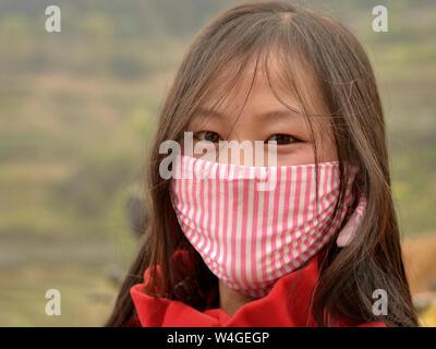 Joven vietnamita con hermosos ojos orientales cubre su nariz y boca con una mascarilla protectora de rayas.