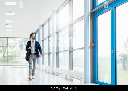 Joven empresario caminando en un pasillo