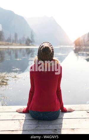 Joven rubia mujer sentada sobre muelle en un lago en invierno
