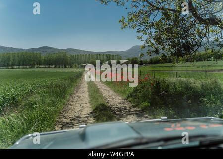 Coche por una pista de tierra en el campo, la Garrotxa, España Foto de stock