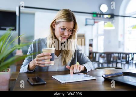 Joven que trabaja con su tableta digital mientras tomaba un café en la cafetería