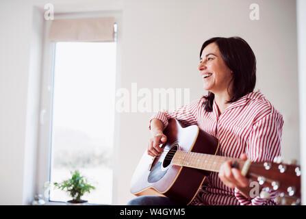 Feliz mujer madura tocando la guitarra en casa