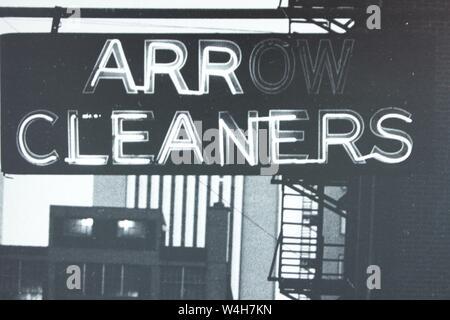 Fino arte fotografía en blanco y negro a partir de la década de 1970 de un cartel de neón de limpiadores de flecha.