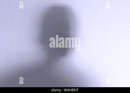 Miedo borrosa cara fantasma detrás de un fondo de vidrio blanco. Orientación horizontal