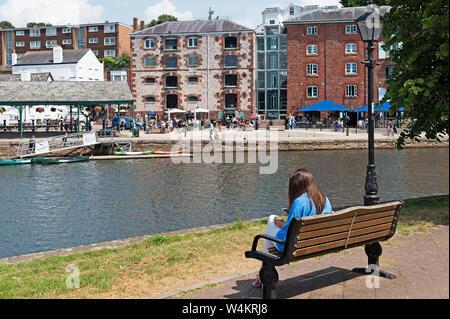 Mujer joven sentado en un banco en el río exe en Exeter, Devon, Inglaterra, Gran Bretaña, Reino Unido.