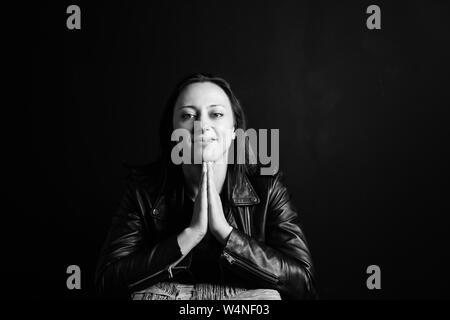 Retrato de estudio de una atractiva mujer joven en una chaqueta de cuero negro contra un fondo liso