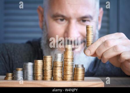 Closeup hombre recoge columnas de multi-monedas de colores de altura creciente, el concepto de acumulación y ahorrar dinero, el enfoque selectivo